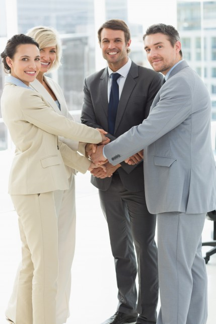 Portrait of business team joining hands together in a bright office